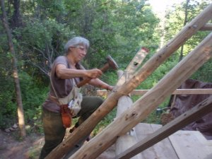 Deanne hammering away at round pole framing