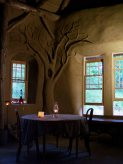 A photo of the interior featuring a beautiful earthen sculpture of a tree and a candlelit table.