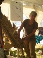 A portrait of Deanne demonstrating thatching technique with a model piece of thatched roof at a natural building colloquium.