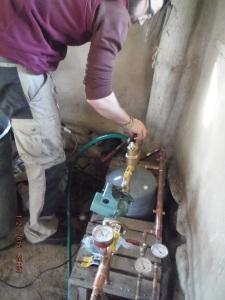 Adam helps with Compost Furnace testing in the Strawbale Studio.