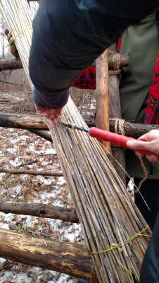 """Hands on with thatching using the ratcheting tool to twist the wire, aka """"Nurse Ratchet"""". The wire attaches the first base layer bundle at an angle over the eave/edge corner to the purlin (batton) cross post on the frame."""