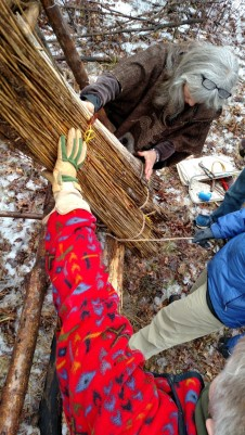 Mary, Deanne, and Heather are seen here tying the base row bundles with manilla rope and a half hitch around the bottom purlin.