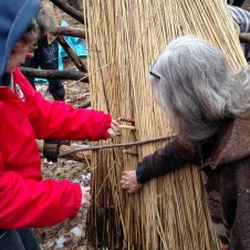 Lynn and Deanne are fastening the sway over the loose reeds. The wooden needle is used to thread through the reed, under the frame's purlin below, and then over the sway.