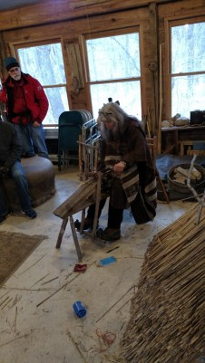Deanne sitting on and demonstrating the draw horse. Her right foot is pushing on the fulcrum to pinch the wood into place as she works on it.